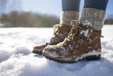 A pair of mountaineer's boots in the snow, close-up shot wearing men's compression socks
