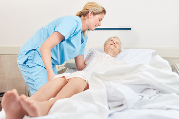 Photo of a nurse helping a bedridden patient