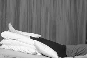 picture of a man with feet elevated,placed on pillows for relieving swollen feet