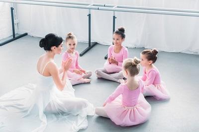 ballet teacher teaching young girls in pink dresses in class