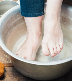picture of a women soaking swollen feet in tub filled with water and epsom salt