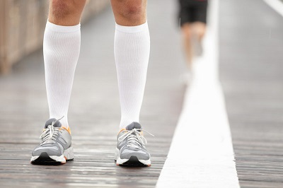 Running shoes closeup and compression socks on male runner.