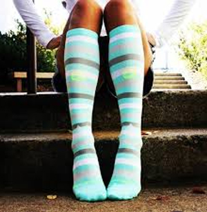 picture of a women sitting outdoors wearing multicolored compression socks