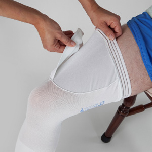 a nurse putting compression socks designed for the clinical purpose, on patient's legs