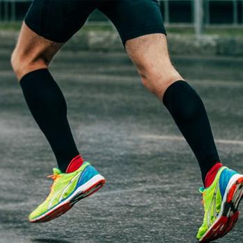 man-running-on-road-wearing-black-compression-socks