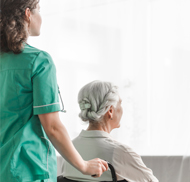 picture of a nurse pushing a wheelchair with old patient sitting on it while wearing graduated knee high clothing to help improve blood circulation