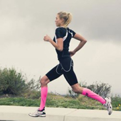 An athlete wearing pink compression socks while on a run