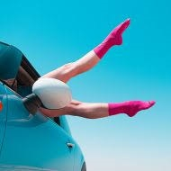 A person wearing pink compression socks with legs dangling out a car window