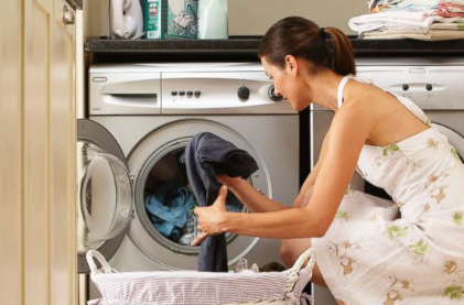 image of woman using a front-loading washer and dryer