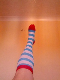 An image of a leg raised wearing a colorful stripped socks