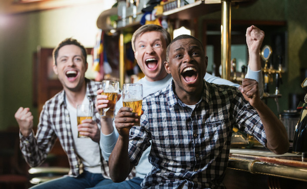 Men cheering in bar with beers in hand