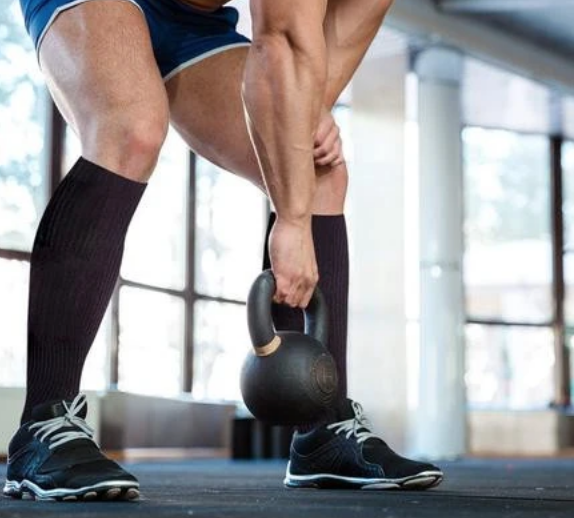 Man in gym with black compression socks on