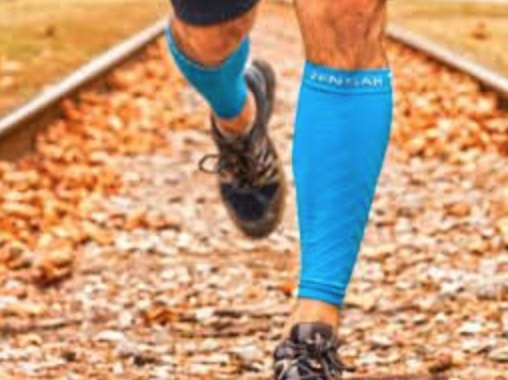 Man running in a pair of blue compression leg sleeves/leg compression sleeves