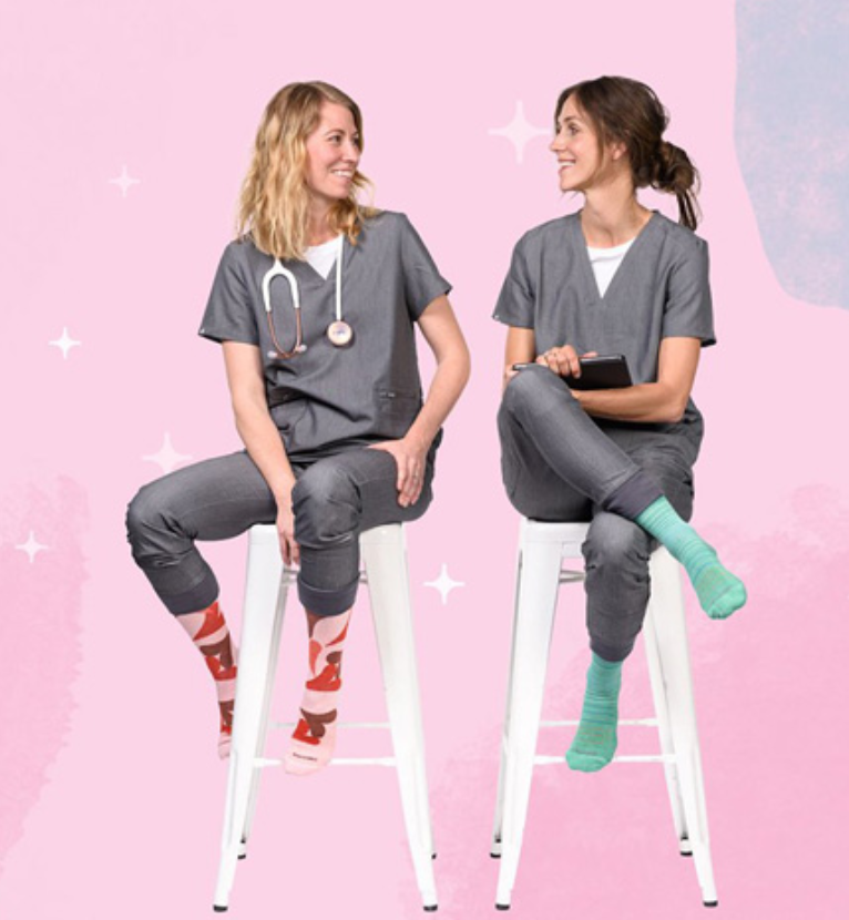 Two nurses chatting while sitting on a chair, wearing scrubs and both wearing compression socks of   different color and design.