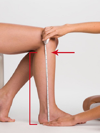 person using measuring tape to measure length of leg