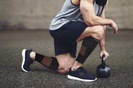 A man exercising with leg compression tubes