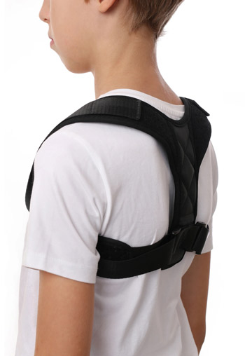 a young boy wearing a back brace on top of his white t-shirt