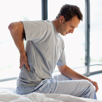 man getting out of bed and experiencing back pains