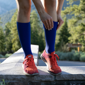Woman donning blue compression socks. These specific compression socks are ComproGear knee high blue Compression Socks in 20-30 mmHg Compression Level.