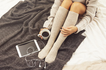 Woman with her coffee in the bed wearing knee high compression socks