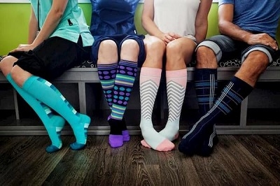picture of men and women wearing knee-high compression multicolored socks