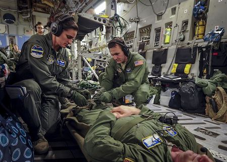 Military Nurses helping a patient. Are they wearing compression socks under their uniforms? I guess we'll never know.