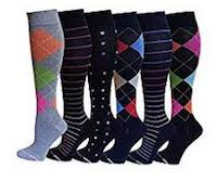 Six compression stockings with varying tux designs that are either grey or black with brightly colored squares on them of orange, pink, blue and green. There are also black stockings with stripes and spots.