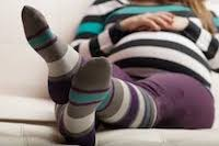 A pregnant woman wearing grey, blue, and purple striped compression socks while relaxing on her couch.