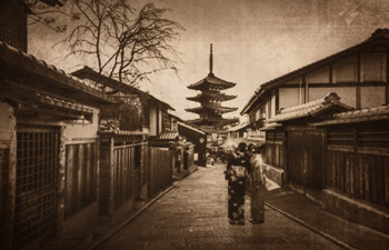 vintage photo of a street scene with 2 Japanese women posing in their traditional Japanese kimono