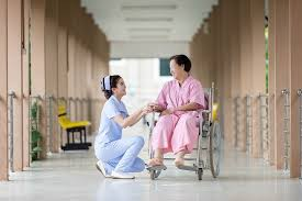 A nurse squats next to a patient in a wheelchair. Her compression stockings help keep her legs energized by preventing swelling and tiredness and improving circulation.