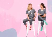 two nurses seated while chatting and showing off their brightly colored compression socks