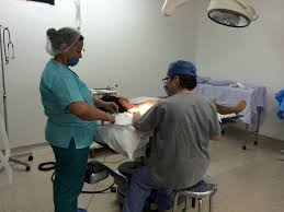 Nurse working on a patient in a hospital operating room. Wearing compression socks helps support blood flow in his legs during a long shift.