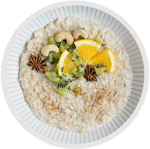 a plate of oatmeal garnished with nuts, star anise, kiwi, and orange wedges