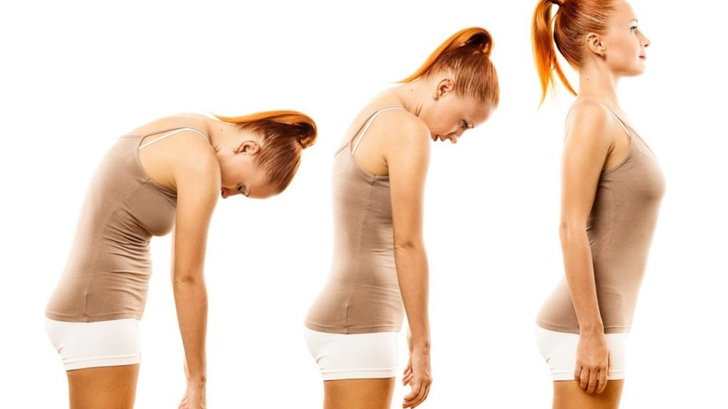 a woman in exercise gear shows how to move from her hunched position to standing up straight and tall