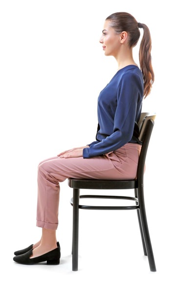 woman demonstrating how to sit properly with her back straight and her feet flat on the floor