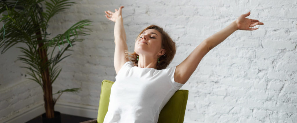 a woman with her arms outstretched takes a deep breath while seated with her back straight against a green chair