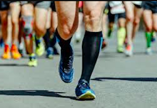 athletes run on the track wearing extra large compression socks