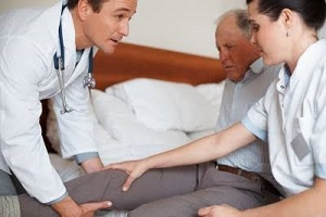 doctors treating a senior man with knee pain with compression socks knee high