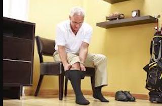 senior puts on socks for compression