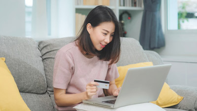 Woman holding her credit card while shopping online