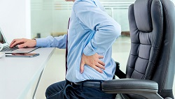 person suffering from back pain due to sitting in one position