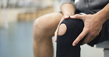 Man holding his knee while wearing a knee sleeve