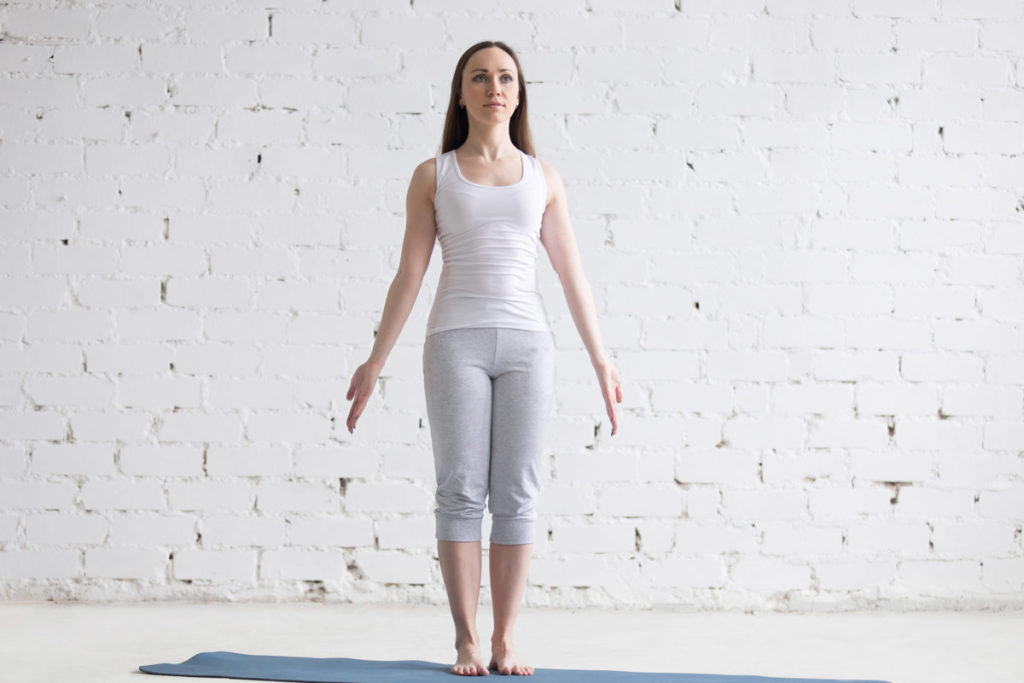 a woman in white exercise clothes assumes a standing position and demonstrates good posture