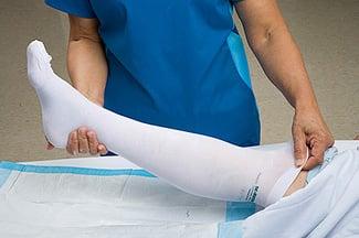 Bedridden patient wearing white knee high compression socks