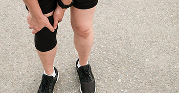Holding her knee with a knee sleeve on after running