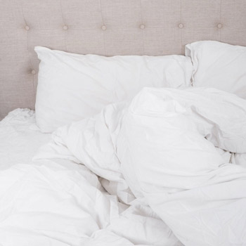 A bed with some white linen including a duvet pushed to one side