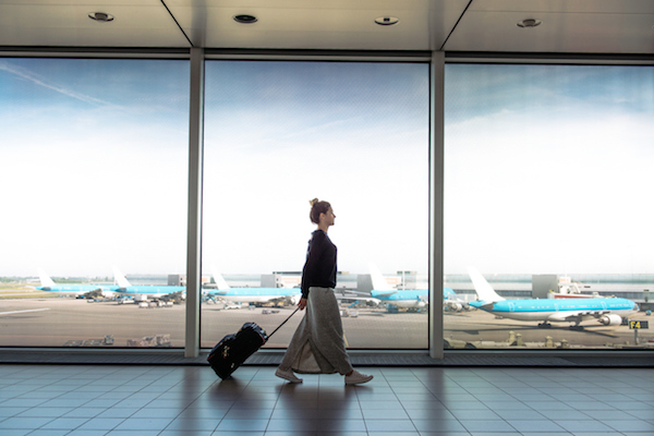 Photo of woman walking with her luggage at the airport