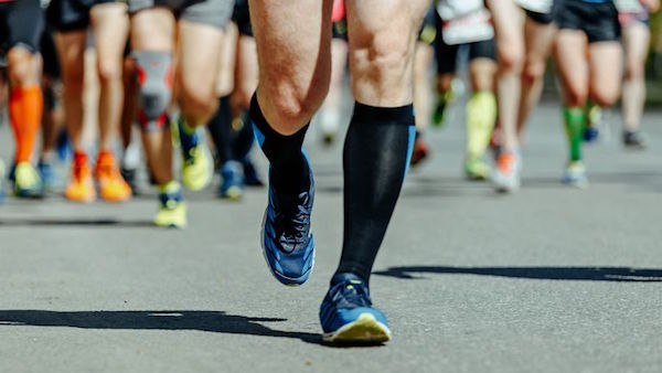Athletes running in knee-high compression socks